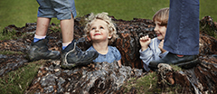 Children playing in an old tree stump taking part in a Family Fun event in the garden at Plas Newydd, Anglesey, Wales.
