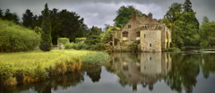The moated fourteenth-century Scotney Castle, Kent, on a beautifully still, though stormy day.