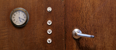Detail of the door handle, lightswitches and clock built into the wall of the Living Room at 2 Willow Road.