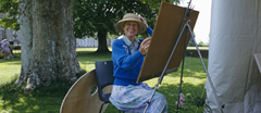 Female artist sitting at her easel at a National Trust Spring Fair at Petworth House, West Sussex.