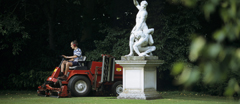 Gardener lawn mowing using a large red sit-on lawn mower, with a marble statue in the garden at Anglesey Abbey.