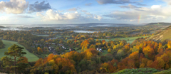 Panoramic view west from Colley Hill, Surrey with morning mist and a rainbow in October.