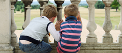 Children looking through the balustrade at Wimpole Hall, Cambridgeshire.
