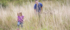 Family exploring the long grass behind the Victorian shooting lodge at Chedworth Roman Villa.