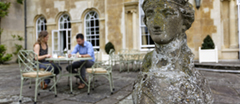 Guests relaxing at a table outside Hartwell House, Buckinghamshire. Hartwell House Hotel, Restaurant and Spa, is part of the Historic House Hotels group.
