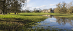 Flooding in the grounds of Lacock Abbey with the house in the distance.