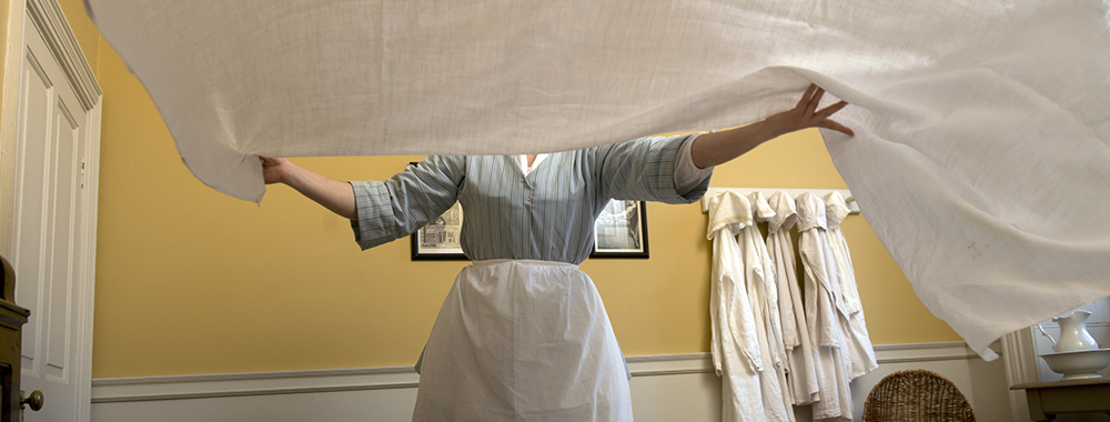 A maid laying a clean white sheet on a bed in the children's bedroom at Wordsworth House and Garden, Cockermouth